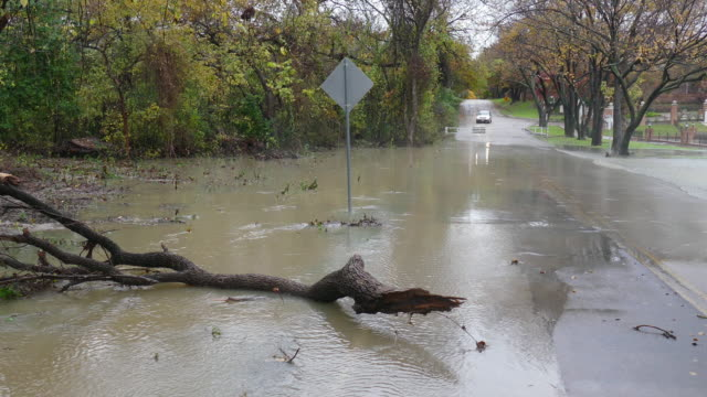 Flooding creek over road past vehicle roadblock Dallas Texas suburb