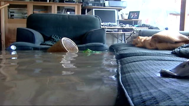 Damage across Britain Arm chair and sofa partially submerged in floodwater with wastepaper basket floating Wooden dining chair tipped over and lying...