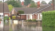 Flooding in Goole People along past parked cars / Street sign 'Mountbatten Mews' PAN flooded road / General views roads and houses submerged in flood...