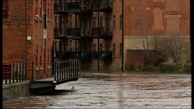 Yorkshire Leeds EXT General view of swollen brown water of River Aire flowing past warehouse buildings / Various of fastflowing river water / More...