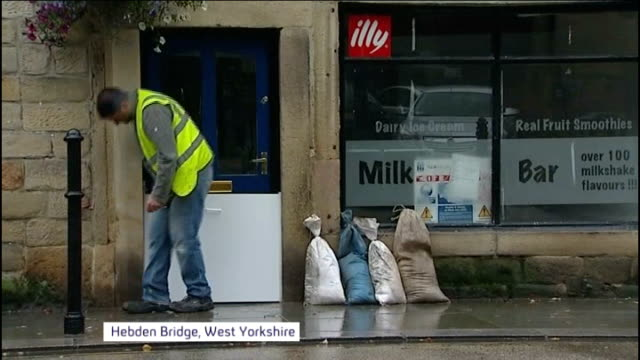 Flooding in Somerset and Herefordshire / Strong winds hit Britain ENGLAND West Yorkshire Hebden Bridge EXT Man putting barrier in doorway of cafe...