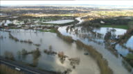 Aerials of RiverThames from Central London through West London and Buckinghamshire AIR VIEWS Flood waters surrounding Chertsey bridge / Digger on...