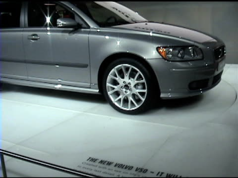 CU floor sign DOLLY OUT to WS of Volvo V50 station wagon revolving on turntable 2005 Volvo V50 station wagon at Cobo Hall on January 14 2004 in...