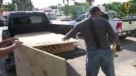 Florida prepares for Hurricane Irma Miami Man cuttgin plywood sheet as boarding windows of building Men boarding up windows of building Man boarding...