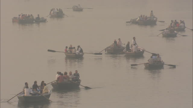 A flotilla of rowboats carries passengers across a river for the Diwali celebration in India.