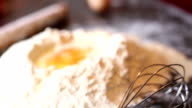 Flour in bowl with eggs and rolling pin
