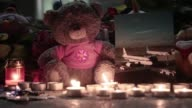 Flowers candles and teddy bears are left outside St