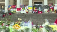 Flowers flags and messages of support adorn a central Brussels square tributes to the 31 dead and 300 wounded in the attacks on the airport and metro
