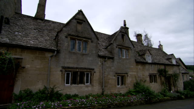Flowers grow along the front of a stone cottage in Gloucestershire, England. Available in HD.