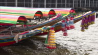 Flowers hang from front of long tail boats docked on the Chao Phraya River in Bangkok, Thailand