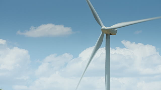 Fluffy Clouds Passing Behind Wind Turbine