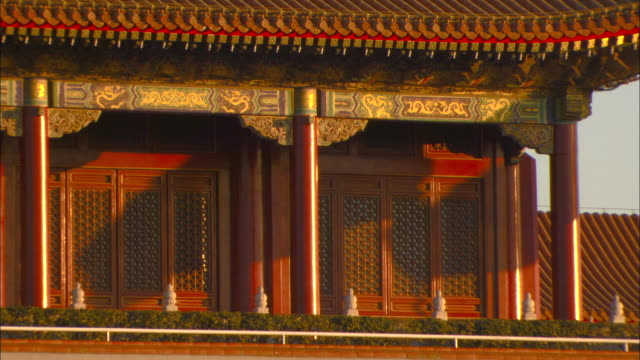 Fluttering flags cast shadows on an ornate building in Beijing's Forbidden City.