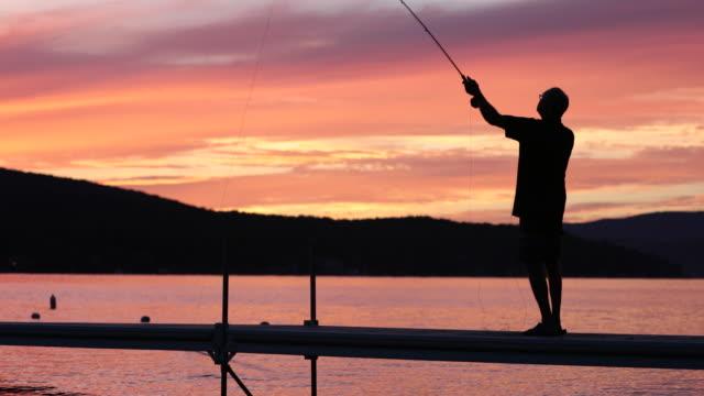 Flugfiske Fisherman siluett på sjön vid solnedgången