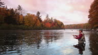 WS PAN Fly-fisherman fishing in river / The Forks, Maine, USA