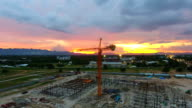 Flying around construction site with dusk sky background