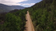 Flying down rocky mountain road with bend - Drone Aerial Video 4K Colorado Rocky Mountains, Colorado river, Mountain dam at lake granby, beautiful water reflection, spring, pristine water, foliage, wildlife aspen trees discovery 4K Nature/Wildlife/Weather