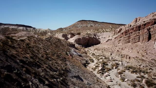 Laag vliegen naar grond door droge rivierbedding in de woestijn