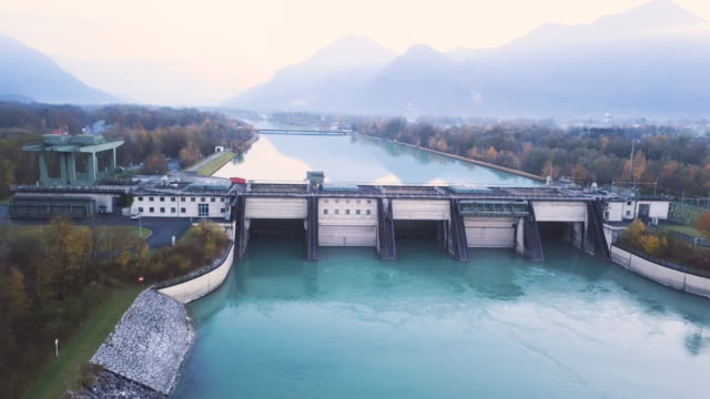 Flying over a hydroelectric dam in an alpine valley at dusk