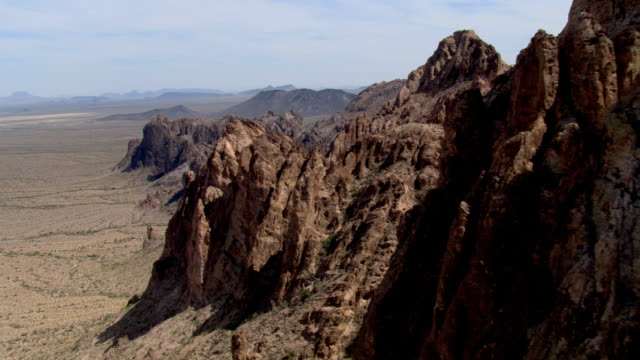 Flying over a jagged rocky ridge in the desert