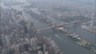 WS Flying over East River Queensboro Bridge Roosevelt Island Upper East Side Queens cityscape on hazy day ZI over highrise rooftops FDR Drive ferry...