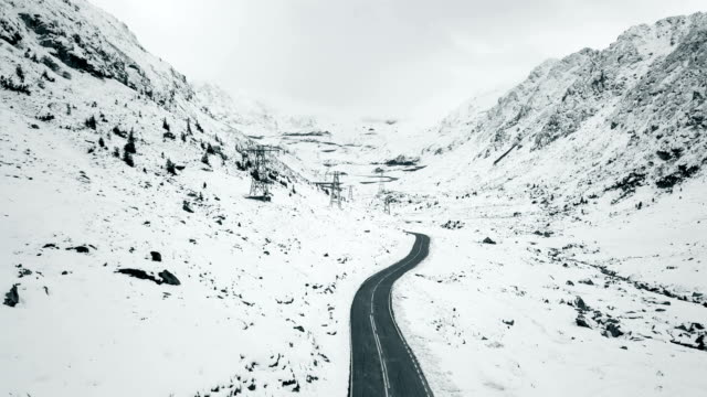 Flying over empty hairpin curve between snowy mountains