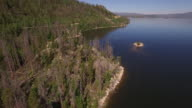 FLying over lake island near shore and road - Drone Aerial Video 4K Colorado Rocky Mountains, Colorado river, Mountain dam at lake granby, beautiful water reflection, spring, pristine water, foliage, wildlife aspen trees 4K Nature/Wildlife/Weather