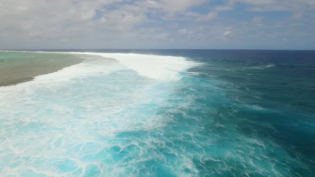 Flying over large breaking waves on Pacific Reef, stormy