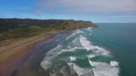 Flying over Piha beach with massive surf waves.
