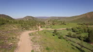 Flying over road to hill - Drone Aerial Video 4K Colorado Rocky Mountains, Colorado river, Mountain dam at lake granby, beautiful water reflection, spring, pristine water, foliage, wildlife aspen trees discovery landscape 4K Nature/Wildlife/Weather