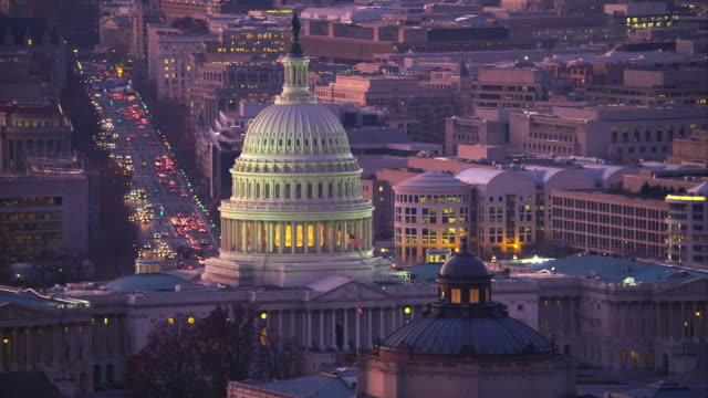 Flying past the Capitol at dusk with Library of Congress in front and Pennsylvania Avenue in background. Shot in 2011.