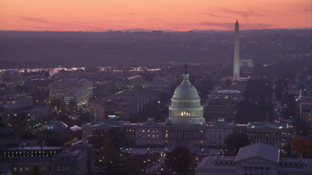 Flying past the Capitol at dusk with Supreme Court Building and Library of Congress in front, National Mall and Washington Monument in background. Shot in 2011.