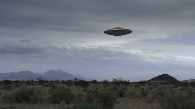 A flying saucer hovers over a windy desert.