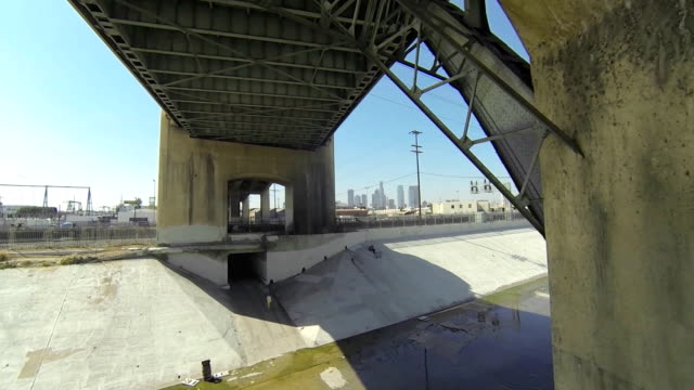 Flying through bridge in Los Angeles River with city in background