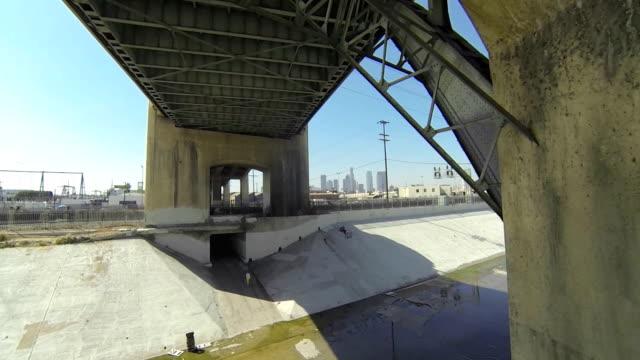 Fliegen durch Brücke in Los Angeles River und die Stadt im Hintergrund.