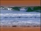 Foamy waves lap on shore as sea twinkles under sky