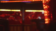 Focus on the red light bulbs of the central 'axle' of a fairground waltzer ride as waltzer cars whizz and spin past, UK.