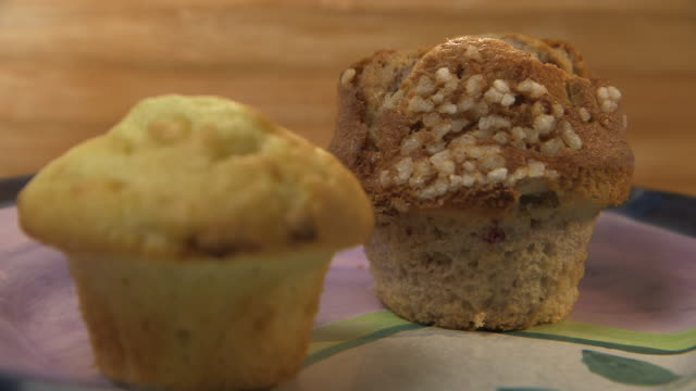 Focus pull between a brown American-style muffin with crystallized sugar in the background to a paler muffin in the foreground.