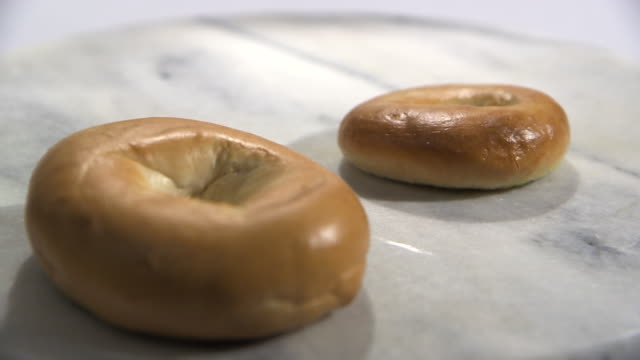 Focus pull between two bagels of different sizes on a marble surface.