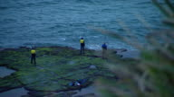Focus pull to three men fishing off the rocks near Austinmer New South Wales Rock platform and gentle swell 2 of the men wear hi viz jackets