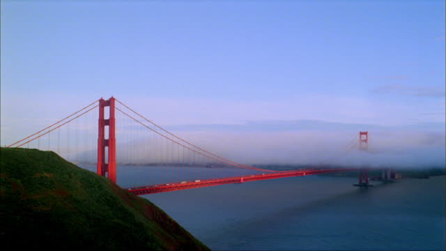Fog and clouds smother the Golden Gate Bridge as daylight turns to night in San Francisco Bay.