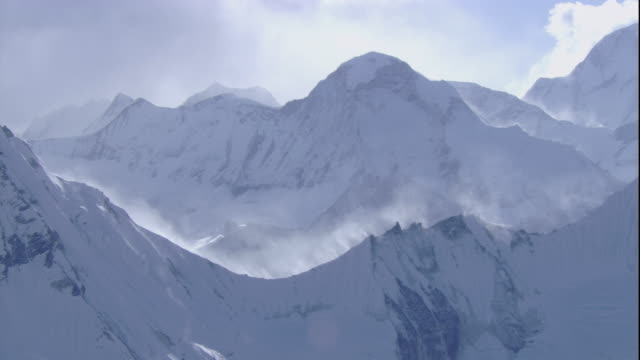 Fog hangs in a valley below the snowy peaks of the Himalaya Mountains in Nepal. Available in HD.