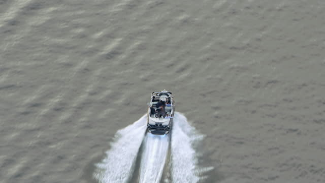 AERIAL Following a speed boat riding on calm water surface