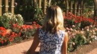 SLO MO POV Following happy young woman walking through summer garden, Lehi, Utah, USA