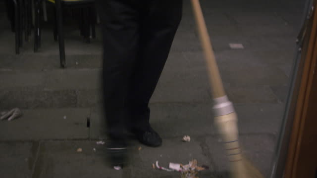Following shot of a man sweeping up the outdoor eating area at an Italian cafe.
