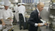POV food being prepared at the hot plating area in a restaurant kitchen; chef looking at incoming orders