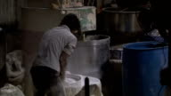 A food service worker sifts large amounts of flour.