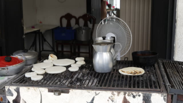 A food vendor is placing dough on a grill at her store in El Vertel a neighborhood with high criminality rate