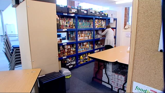 Foodbanks struggling to cope with sharp rise in demand Tins being put on shelf by volunteer Close Shot 'Client Testimony' note on notice board PAN...