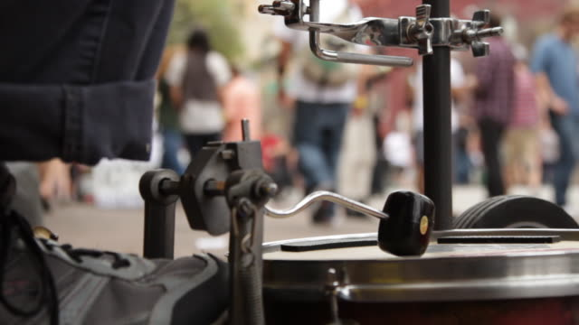 Foot On Drum Pedal With People Passing By