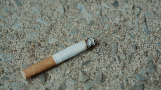 Foot turns off smoking cigarette Healthy choice on street sidewalk